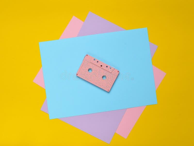 在淡色色纸背景的卡型盒式录音机 减速火箭的媒介技术80s 音乐,娱乐 顶视图 简单派趋向 免版税库存图片