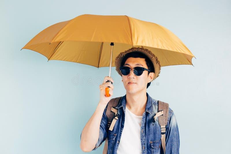 在淡色蓝色背景的年轻亚洲旅游举行的伞 单独和正在寻找伙伴旅行 库存图片