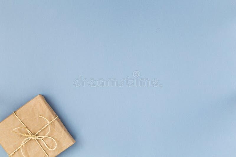 在淡色蓝色背景的牛皮纸或当前箱子包裹的顶视图礼物 平位置称呼 复制文本的空间 免版税库存照片