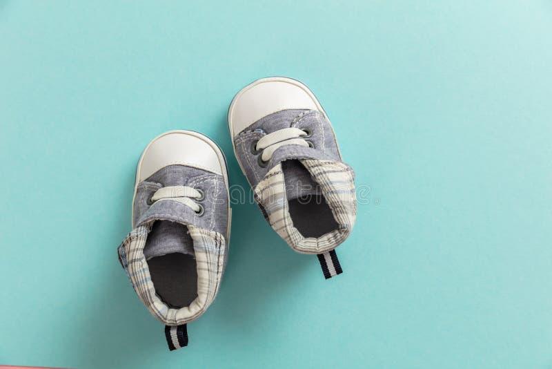 在淡色蓝色背景的男婴鞋子 库存照片