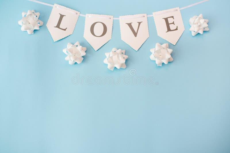 在淡色蓝色背景,与拷贝空间的顶视图的词爱 情人节或抽象爱概念 图库摄影