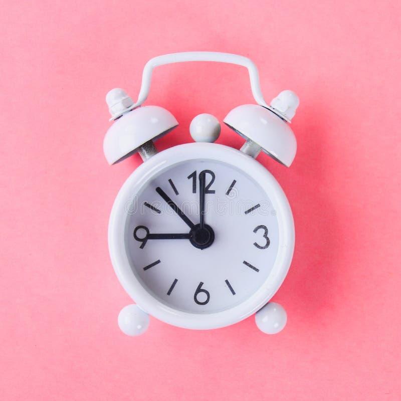 在淡色蓝色,桃红色背景的白色闹钟 免版税库存图片