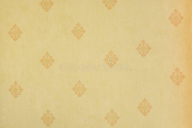 在淡黄色墙壁上的摘要米黄花卉样式-织品,纹理,反复 免版税库存照片
