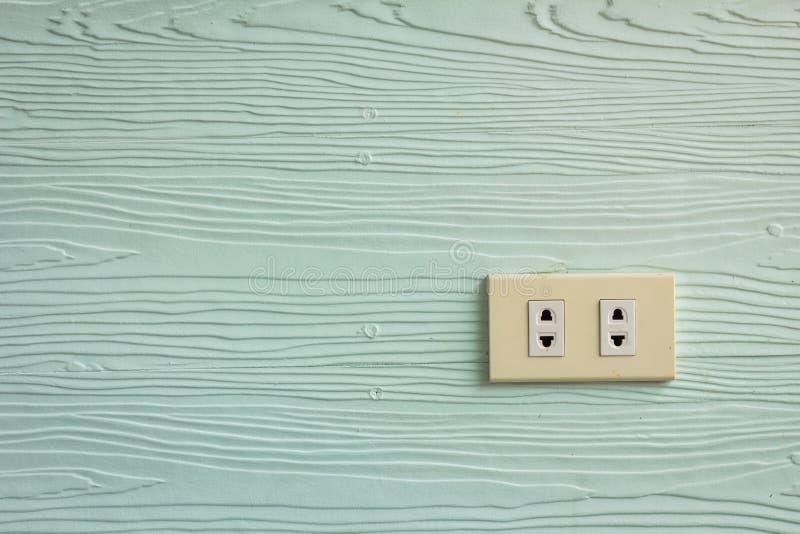 在淡绿色的墙壁上的壁装电源插座有木纹理的 免版税图库摄影