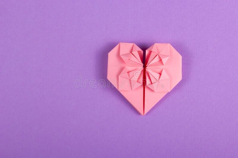在淡紫色背景的桃红色华伦泰origami 纸张的重点 免版税库存图片