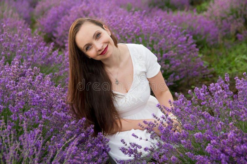 在淡紫色领域中的微笑的妇女 库存图片
