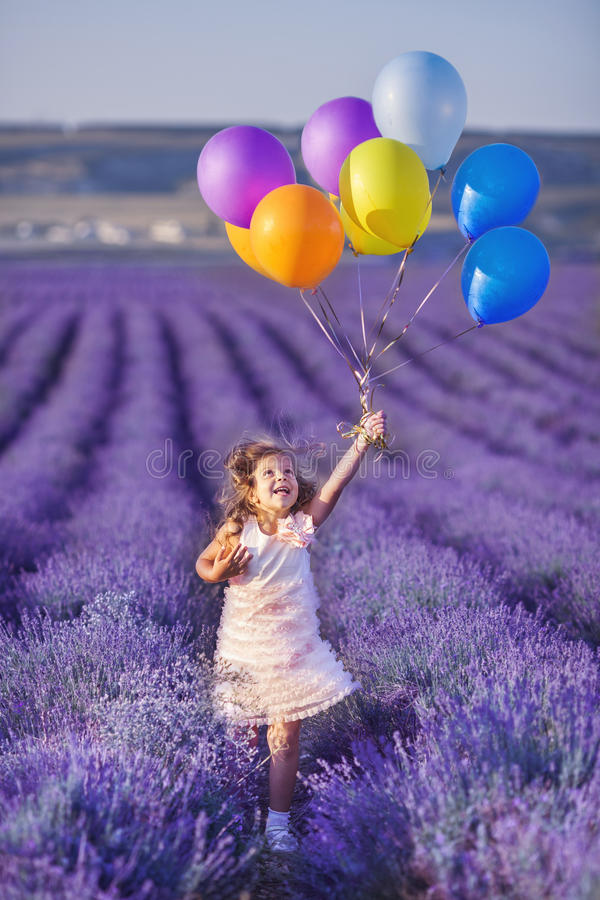在淡紫色领域的微笑的女孩嗅花 免版税库存图片