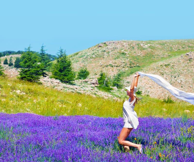 在淡紫色领域的美好的女孩跳舞 免版税库存照片