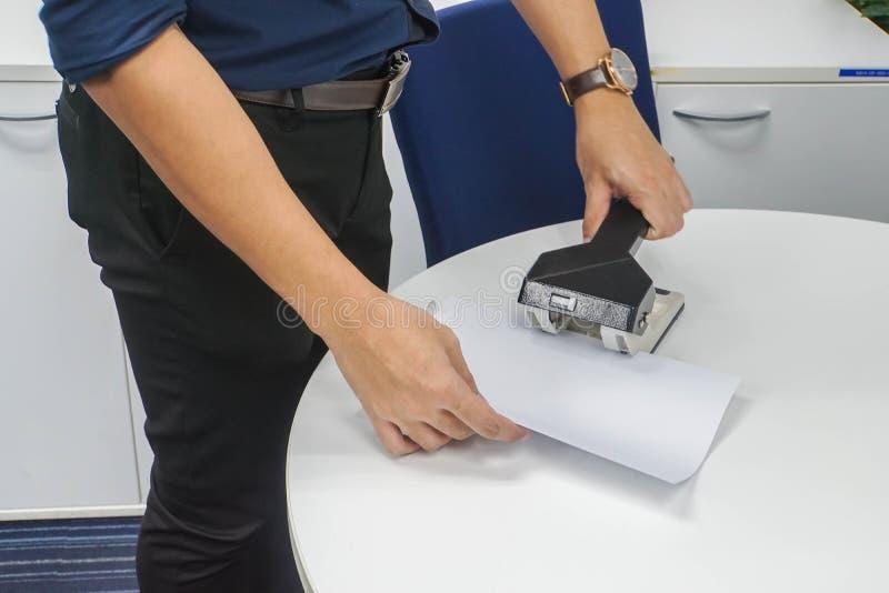 在深刻的蓝色保留商业文件的衬衣用途大拳打的商人在办公室归档 免版税库存照片