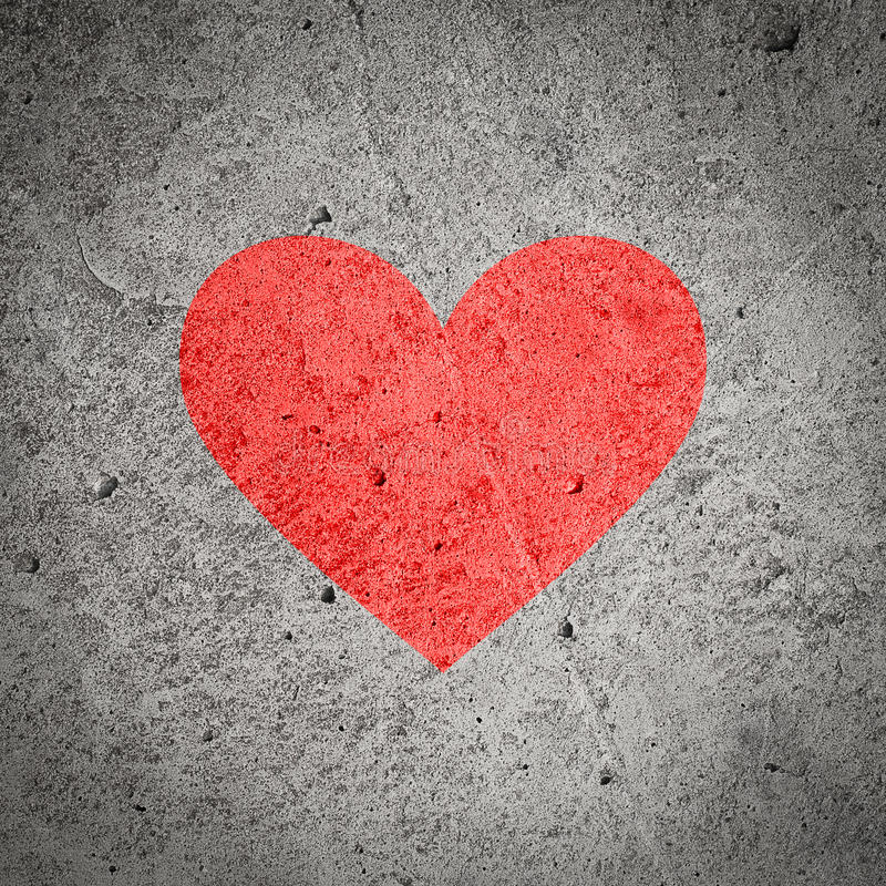 在深灰混凝土墙,织地不很细背景上的被绘的红色心脏 库存照片