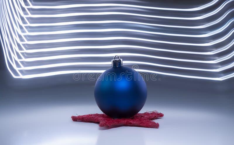 在深灰背景光线影响的一个唯一蓝色圣诞树球 免版税库存图片