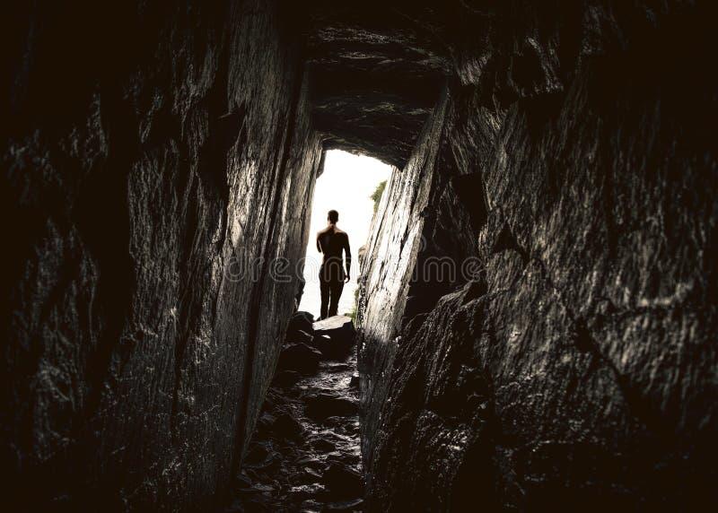 在深窄洞穴入口的人 图库摄影