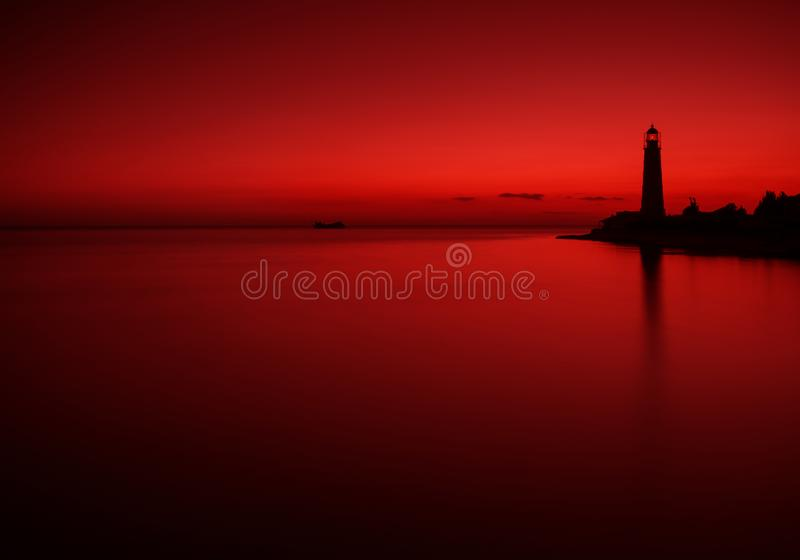 在深红口气的海风景与一艘凹下去的船和一座老灯塔的剪影 在红颜色的海景 艺术性的场面 库存照片