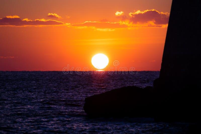 在深红天空的太阳设置沿堡垒墙壁到有反射的海洋里在杜布罗夫尼克,克罗地亚 库存图片