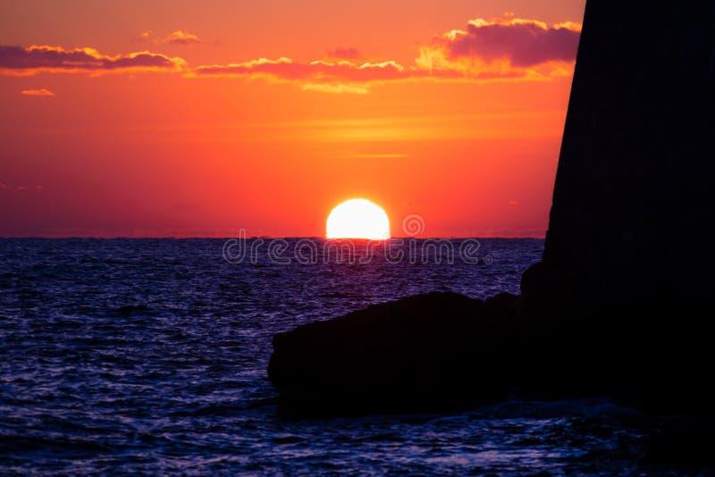 在深红天空的太阳设置沿堡垒墙壁到海洋里在杜布罗夫尼克,克罗地亚 图库摄影