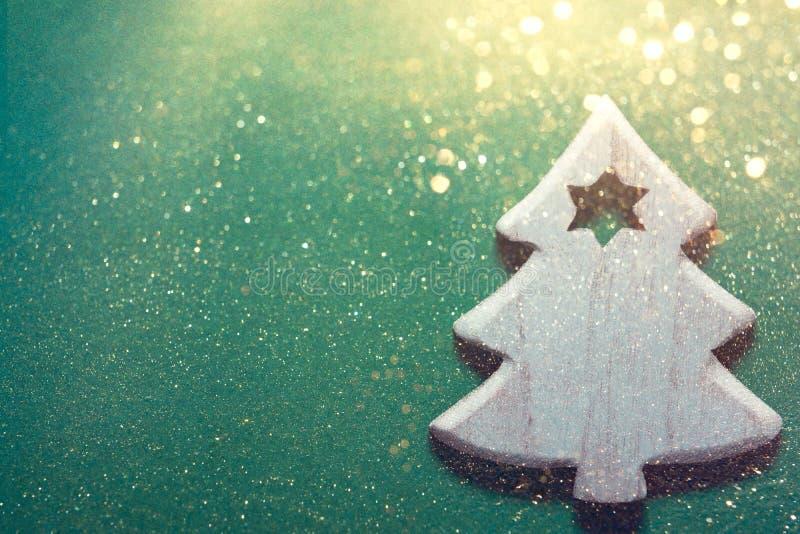 在深绿背景的木装饰品圣诞树在闪耀的光金黄闪烁 创造性的欢乐新年假日 免版税库存图片