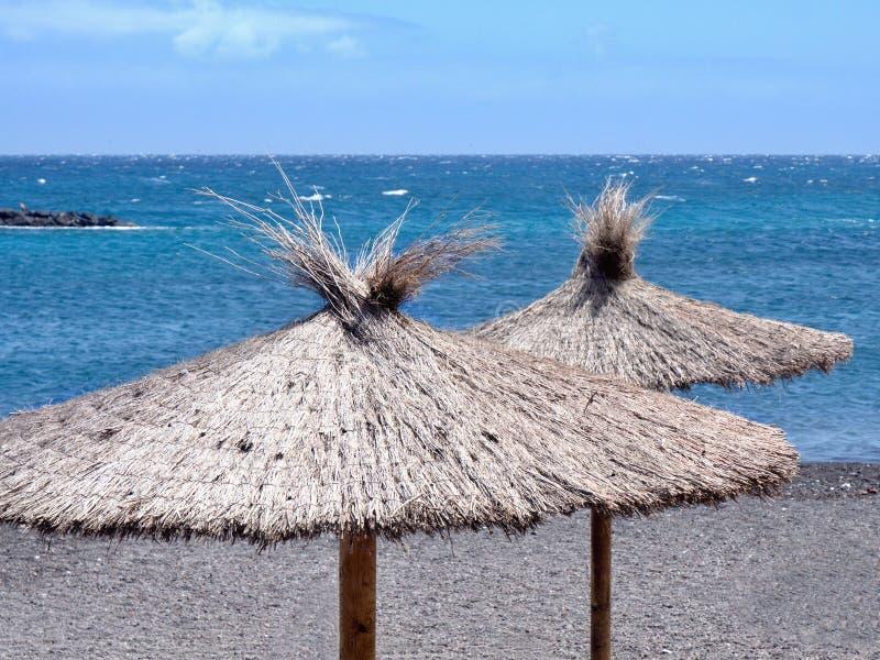 在深蓝大西洋前面,两把芦苇草遮阳伞支持水 免版税库存照片