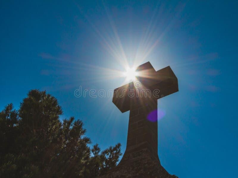 在深蓝天空背景的基督徒石十字架反对太阳 r 免版税库存图片