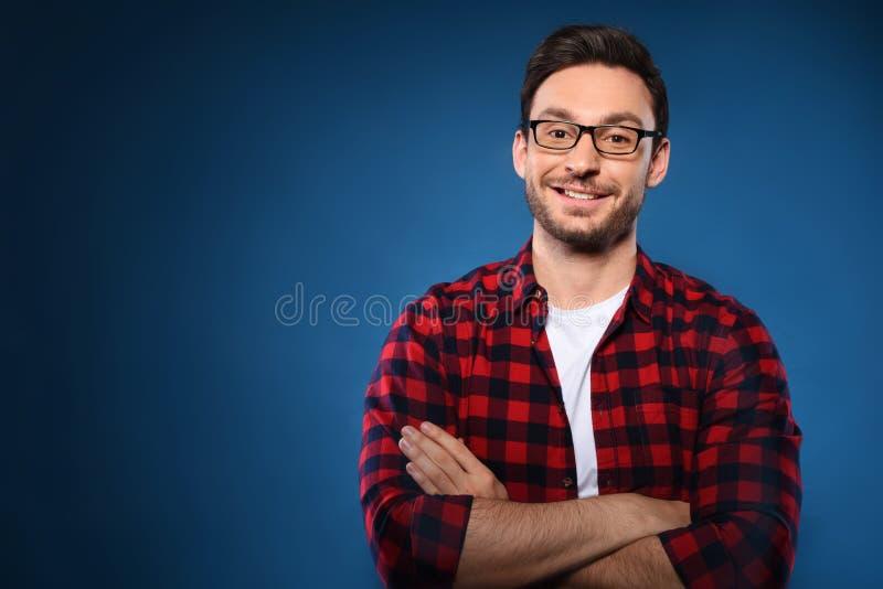 在深蓝背景和红色衬衣的英俊的有胡子的人隔绝的玻璃认为并且微笑着 库存照片