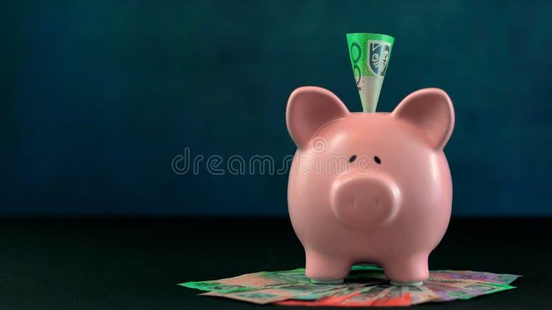 在深蓝背景的桃红色存钱罐金钱概念 库存照片