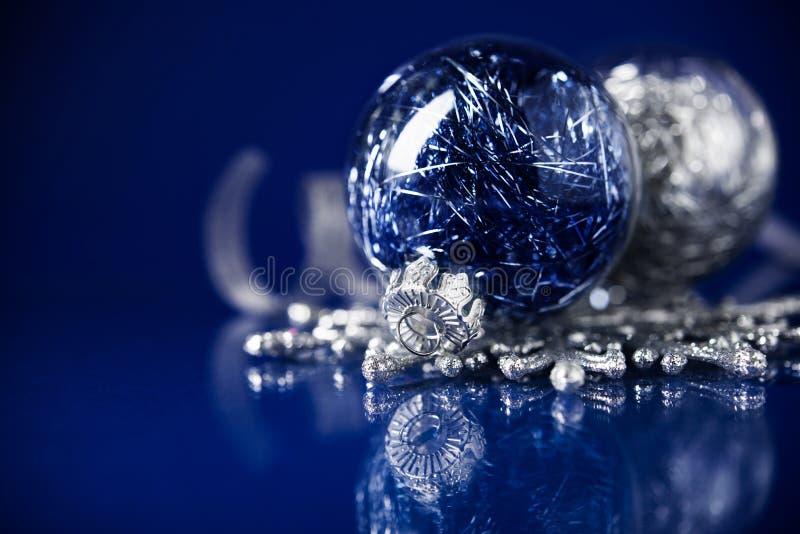 在深蓝背景的银色和蓝色圣诞节装饰品 圣诞快乐看板卡 免版税图库摄影