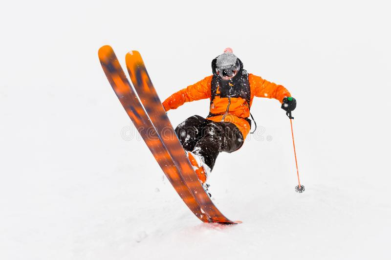 在深雪外面的专业滑雪者运动员乘驾,当执行一个滑雪的把戏在暴风雪时 冬天季节是  免版税图库摄影