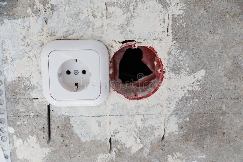 在混凝土墙上的电子插口孔 建设中电子插口关闭 库存图片
