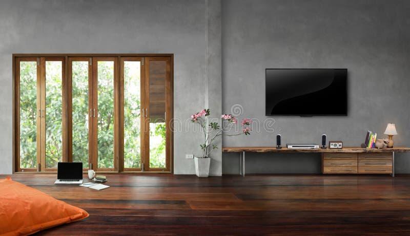 在混凝土墙上的电视有在客厅内部的高窗口的 图库摄影