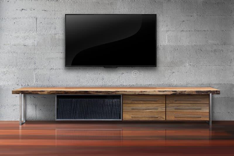 在混凝土墙上的被带领的电视有木桌客厅的 免版税库存照片
