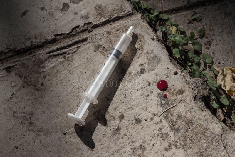 在混凝土户外-接近的药物概念的被放弃的注射器我 免版税图库摄影