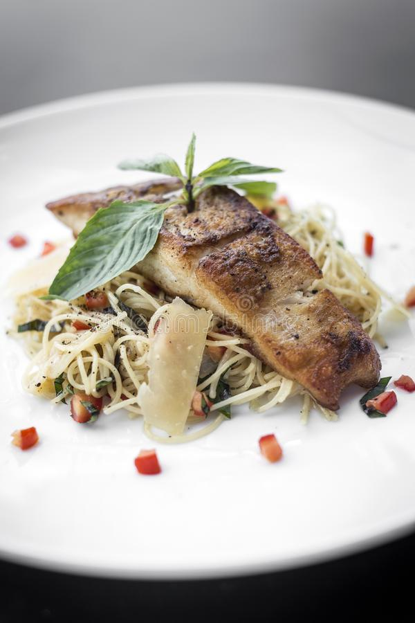 在混杂的菜和巴马干酪意粉面团的新鲜的鳕鱼内圆角 库存图片