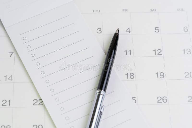 在清单的笔与在干净的日历的复选框笔记薄使用作为特别活动、计划者、重要提示或者任命名单 库存照片