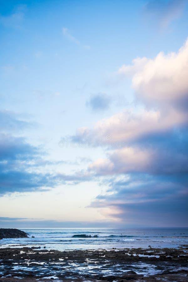 在清早sunrsie的风景风景海洋岩石的靠岸和年轻冲浪者的波浪背景的 蓝色美丽的天空 免版税库存图片