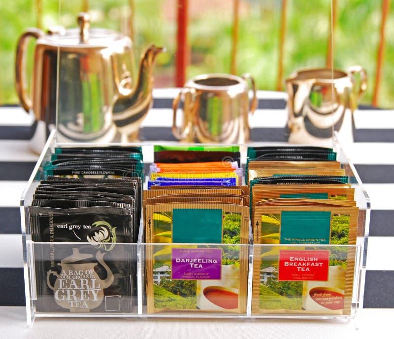 在清楚的丙烯酸酯的茶包持有人的茶袋与银器罐集合 免版税库存图片
