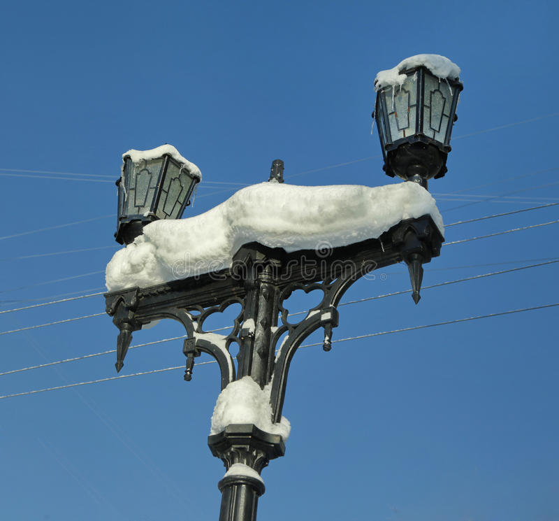 在清楚的天空和导线背景的积雪的路灯柱  免版税库存图片