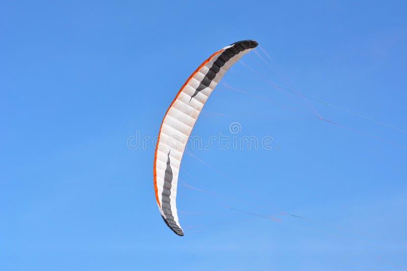 在清楚的天空蔚蓝前面的大弓风筝飞行 免版税库存照片