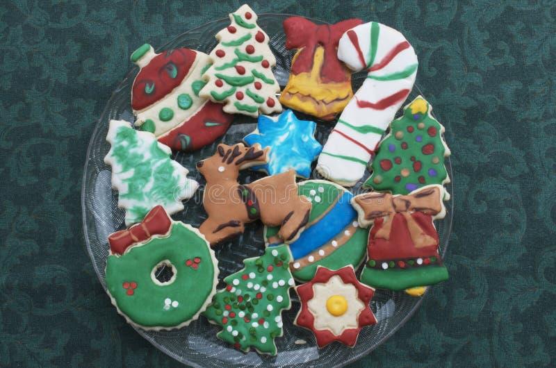 在清楚的板材,绿色桌布的自创装饰的保险开关圣诞节曲奇饼 免版税库存照片