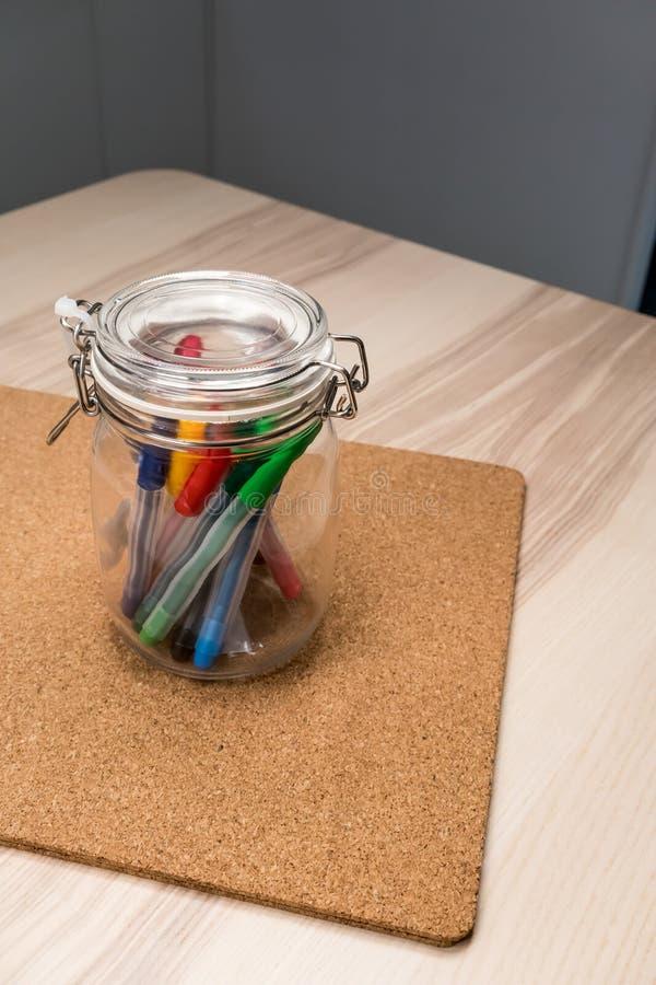 在清楚的玻璃环绕形状持有人的记号笔书桌的组织 库存图片