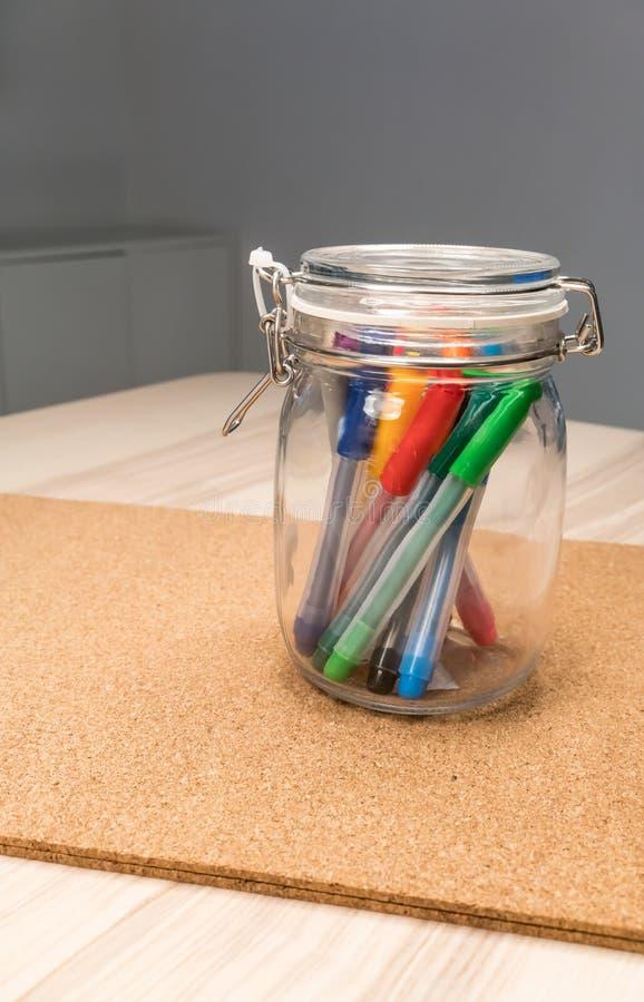 在清楚的玻璃环绕形状持有人的记号笔书桌的组织 图库摄影