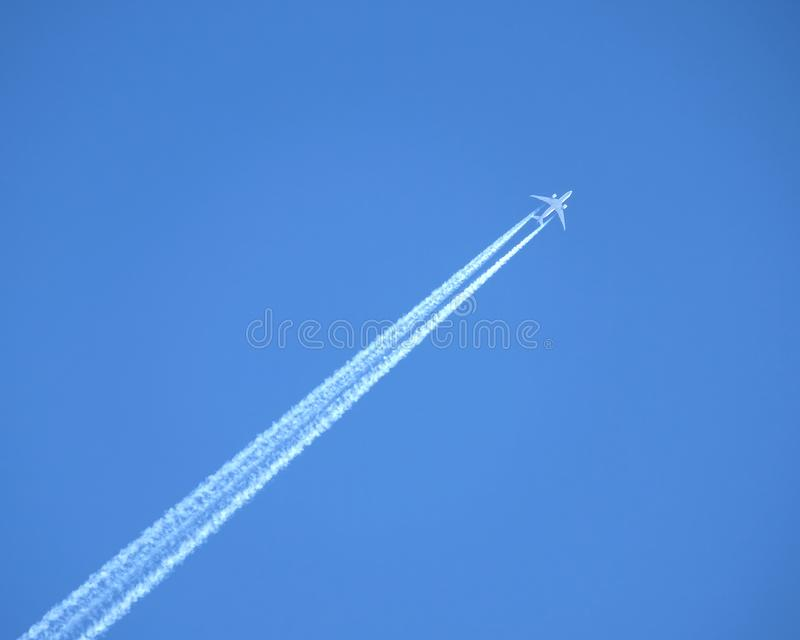 在清楚的蓝天的喷气式客机飞行,离开白色足迹 免版税库存照片