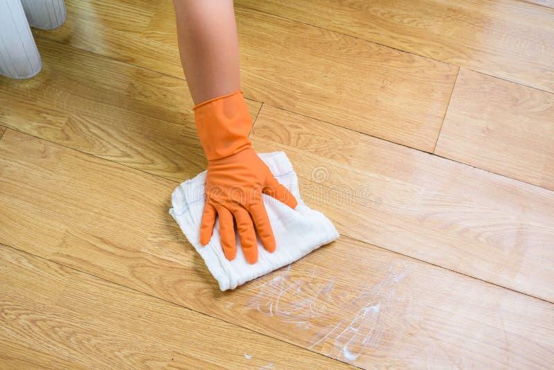 在清洗木地板的手套的手与旧布和清洁剂在 图库摄影