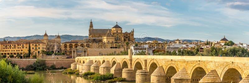 在清真寺大教堂的全景有罗马桥梁的在科多巴,西班牙 免版税库存照片
