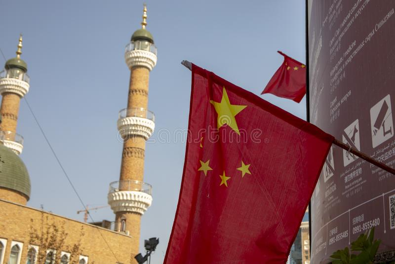 在清真寺旁边的中国旗子有被发出的安全警告的, Urumch 免版税库存图片