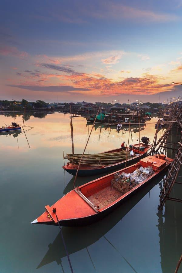 在渔夫村庄的小渔船有日落的 库存图片