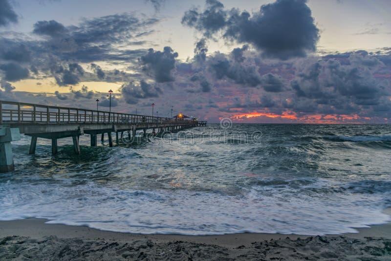 在渔码头的日出有大波浪的 图库摄影