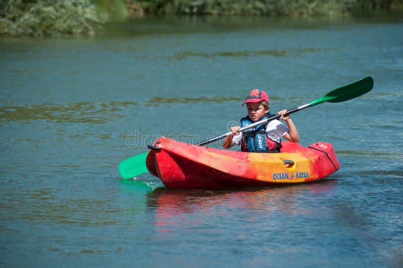 在渠道的小男孩划船在橙色皮船 免版税库存照片