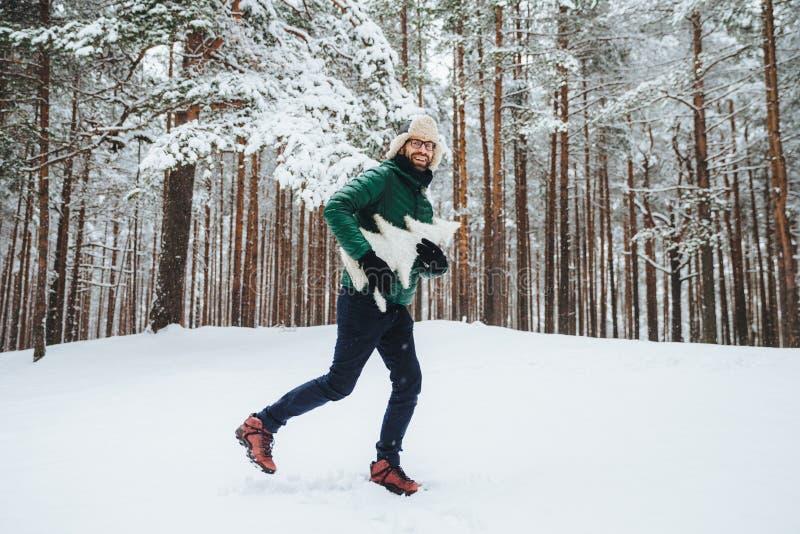在温暖的冬季衣服穿戴的乐观年轻男性,获得室外的乐趣在冬天森林,呼吸新鲜空气,高兴看雪,h 免版税库存图片
