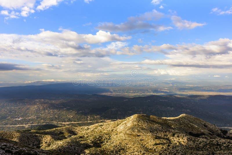 在温暖的平衡的光的小山与反对天空蔚蓝和白色云彩,Biokovo自然公园的贫瘠植被 免版税库存图片