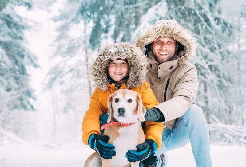 在温暖的戴头巾偶然附头巾皮外衣夹克外衣和儿子打扮的父亲走与他们的小猎犬狗在快乐多雪的森林里 免版税库存照片