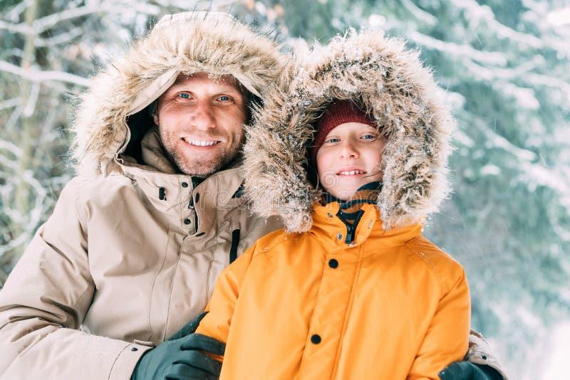 在温暖的戴头巾偶然附头巾皮外衣夹克外衣和儿子打扮的父亲走在多雪的森林快乐的笑容画象 免版税图库摄影